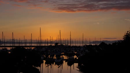 Time lapse video shows sun setting beyond the boats at The Berkeley Marina in the San Francisco Bay