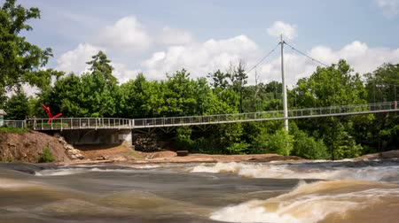 Time lapse video show fast clouds and people at The Liberty Bridge at Falls Park on The Reedy River in Greenville, South Carolina