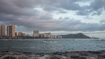 Time lapse video at sunset of Waikiki Beach and Diamond Head on the beautiful Hawaiian Island of Oahu. Video depicts fast moving clouds, waves, boats and people.