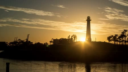 Sun setting behind light house in silhouette at Shoreline Village in Long Beach, Californnia
