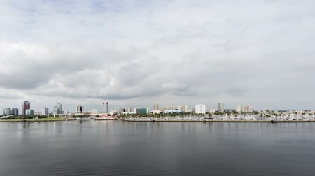 Seamless loop time lapse video of Shoreline Village and downtown Long Beach with fast moving clouds and passing boats.