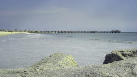 Waves crashing on the coastline of Seal Beach with Seal Beach Pier in background seamless time lapse loop video