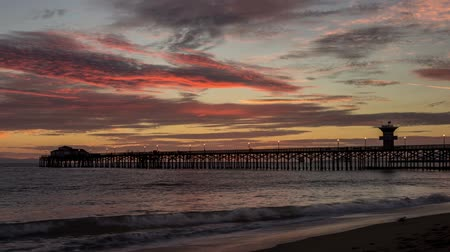 Time lapse video captures fast moving clouds, waves, and sun setting at the Seal Beach Pier in Seal Beach, California