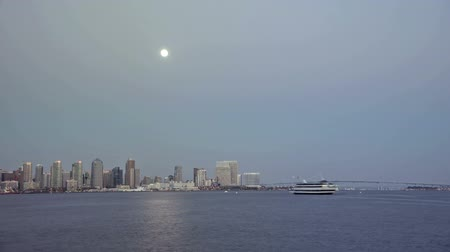 Time lapse video of moon rising over San Diego Bay at twilight with downtown cityscape and passing boats Wideo