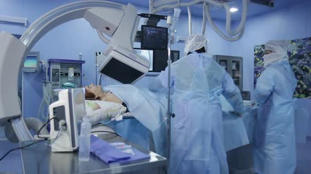 chirurgie : Angiographic operating: nurse helps to the three surgeons during surgery