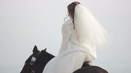 Happy bride and groom riding on horses at the seashore