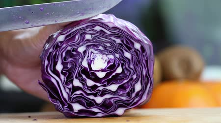 food preparation : Hand slicing a purple cabbage with a knife, close up, HD 1080P