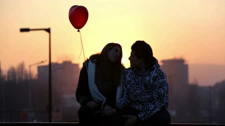 casal heterossexual : Sofia, Bulgaria - February 14, 2015: A silhouette of an young couple in love with a red heart shape balloon sitting on a bridge at the night of Valentines Day. Stock Footage