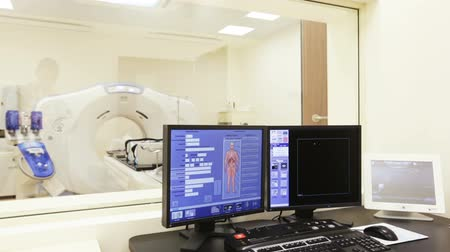 skenovat : A scanning room with computers and monitors next to the CT scan room in a new modern cancer treatment hospital. Zoom out.