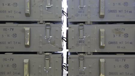 munitions : Green ammunition boxes with rocket-propelled grenades (RPGs) in a munition producing factory. Highly dangerous explosives. Ready for shipping in green closed military boxes. Zooming out.