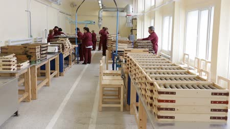 munitions : Sopot, Bulgaria - May 17, 2016: Rocket explosives for anti tank rocket-propelled grenades (rpgs, bazooka) into boxes in a munition producing factory. Workers working at the background.