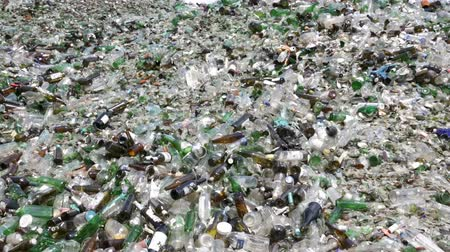reprocessing : Glass waste for recycling in a recycling facility. Different glass packaging bottle waste. Glass waste management. Process of waste glass into usable products. Pile of different bottles. Zooming out.