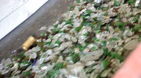 reprocessing : Glass particles for recycling in a machine in a recycling facility. Different glass packaging bottle waste. Glass waste management. Glass recycling is the process of waste glass into usable products.