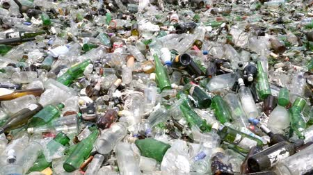 reprocessing : Glass waste for recycling in a recycling facility. Different glass packaging bottle waste. Glass waste management. Process of waste glass into usable products. Pile of different bottles. Panning.