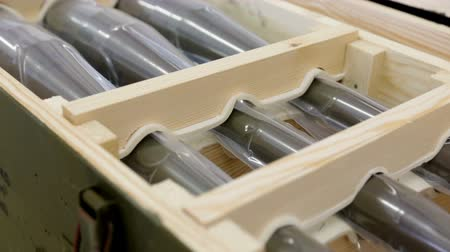 munitions : Six anti tank rocket-propelled grenades (bazooka) into a box in a munition producing factory. Highly dangerous explosives. Ready for shipping in green military boxes. Zooming out. Stock Footage