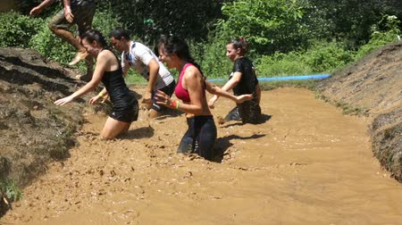 bahno : Sofia, Bulgaria - July 9, 2016: Participants are jumping into muddy water at the Legion Run extreme sport challenge near Sofia. The sports event is mud and obstacle course designed to test peoples physical strength, stamina, and mental grit.