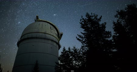 Rozhen astronomical observatory under the night sky stars. Blue sky with hundreds of stars of the Milky way. Observatory in a pine trees forest in the mountain. Moon light. Vignetting. Zoom and tilt 4k.