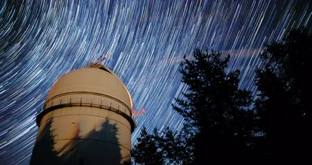 Rozhen astronomical observatory under the night sky stars. Blue sky with hundreds of stars of the Milky way. Observatory in a pine trees forest in the mountain. 4k timelapse in comet mode. Tilting