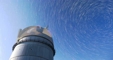 Rozhen astronomical observatory under the night sky stars. Blue sky with hundreds of stars of the Milky way. 4k timelapse in comet mode.