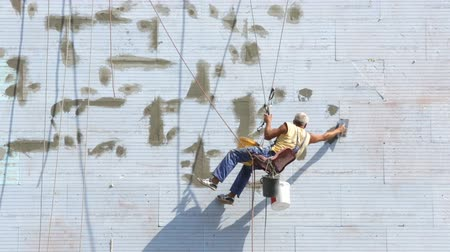 A worker putting on a buildings thermal and noise isolation is working hanging on ropes on the wall of the building.