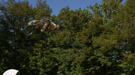 adrenalin : Sofia, Bulgaria - September 24, 2016: An extreme rider is making a free style jump from a ramp. The young boy with his bicycle is seen up in the air near trees. Dostupné videozáznamy