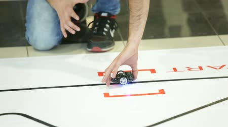 self made : A student prepares and starts his race robot during an open competition of self-made robots among school students. Stock Footage