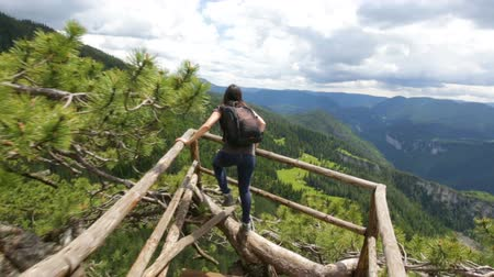 túnel : Young tourist woman with backpack runs to the view from a wooden bridge high in the mountain designed for viewing the side from above. In pine trees. Vivid image of the mountain. Tourism destination. Stock Footage