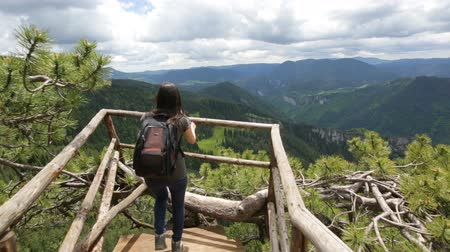 túnel : Young tourist woman with backpack enjoys the view from a wooden bridge high in the mountain designed for viewing the side from above. In pine trees. Vivid image of the mountain. Tourism destination.