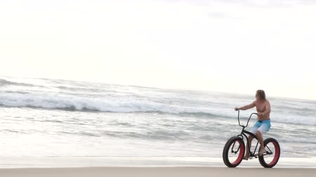 Bike riding on the ocean shore early in the morning Wideo