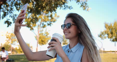 atividade de lazer : Beautiful girl taking selfie while holding coffee cup at the public park