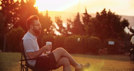 Handsome man drinking coffee in public park at sunset Stok Video