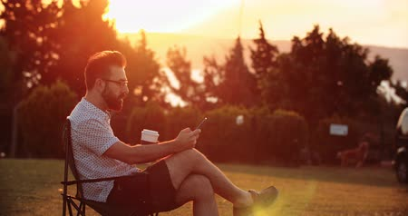 Handsome man using smartphone while drinking coffee in public park at sunset