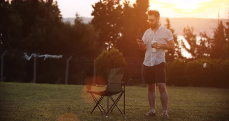 Video Handsome man using smartphone while drinking coffee in public park at sunset