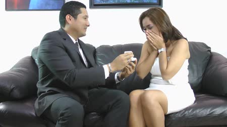 affairs : Wedding proposal; Happy young man giving a ring to a beautiful surprised young woman.