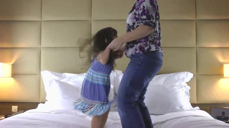 salto : mother and daughter jumping on bed