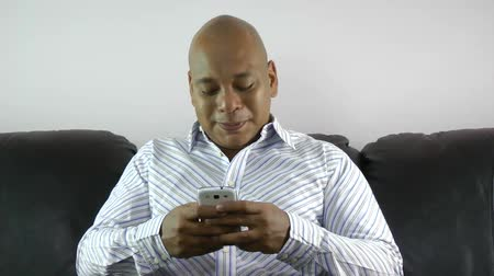afro amerikai : african american businessman using smart phone emailing at home