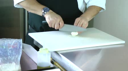 food preparation : Cropped view of the hands of a man slicing a mushroom with a kitchen knife on a chopping board