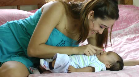 испанец : young hispanic woman playing with her little baby in bed