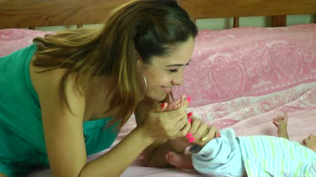 ayaklar : happy young hispanic mother kissing her two months old sons feet in bed at home