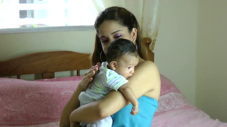 detém : Hispanic Latina mother holding drooling baby over shoulder and tapping on back so infant can burp Vídeos