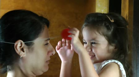 palyaço : silly girl puts clown nose on mother Stok Video