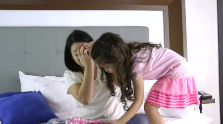 подарок : Little girl giving a gift to her mother in the bedroom. She close her eyes.