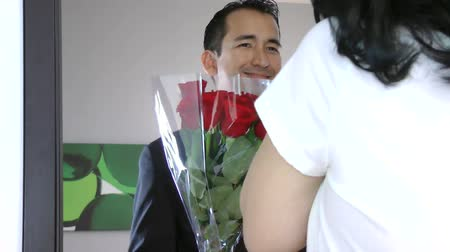 namorado : Handsome man giving a bouquet of red roses to his girlfriend