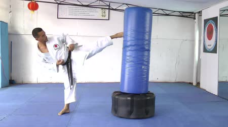 каратэ : Black belt Karate Man practicing in the sandbag