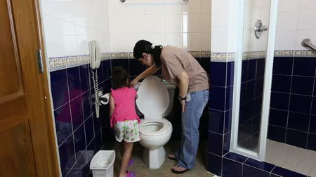 toilets : mother teaching her baby to use the toilet Stock Footage