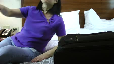 bagagem : young tired woman with luggage on bed