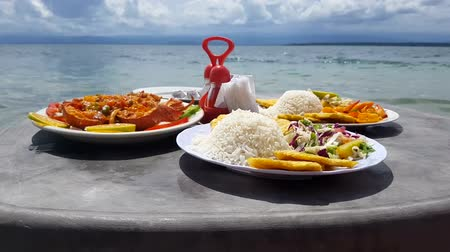 Closeup view of caribbean food served in table on the beach. Vídeos