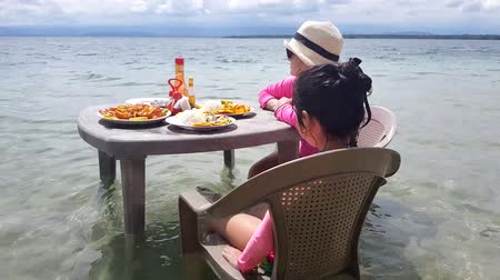servido : Mother and daughter ready to eat on a table in the beach