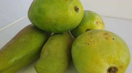 Пакистан : Close up of mangoes on a White background. It is the national fruit of India and Pakistan, and the national tree of Bangladesh Стоковые видеозаписи
