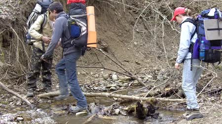 hiking : Hikers cross a brook. One helps another.